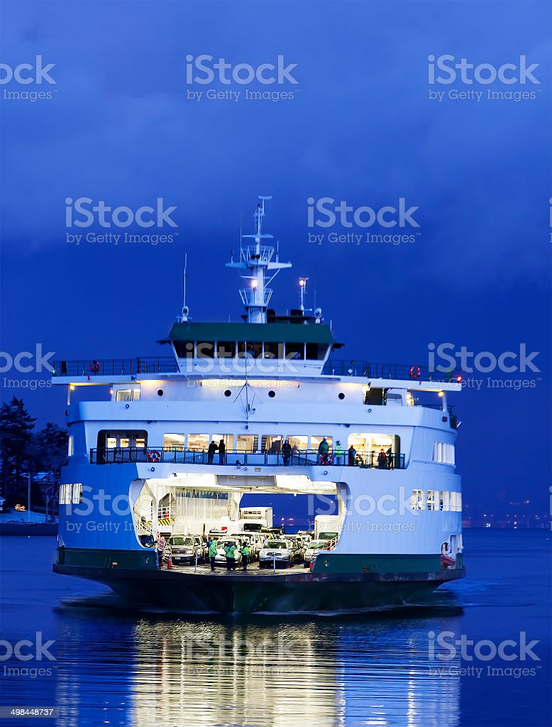 Crowded Car and Passenger Ferry Arriving after Dusk stock photo