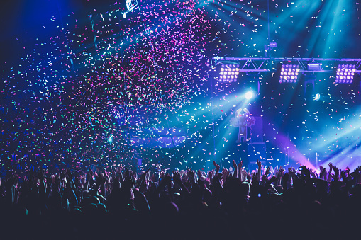 A crowded concert hall with scene stage lights, rock show performance, with people silhouette, colourful confetti explosion fired on dance floor during a concert festival
