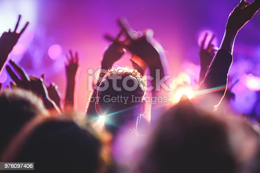 istock A crowded concert hall with scene stage lights, rock show performance, with people silhouette 976097406