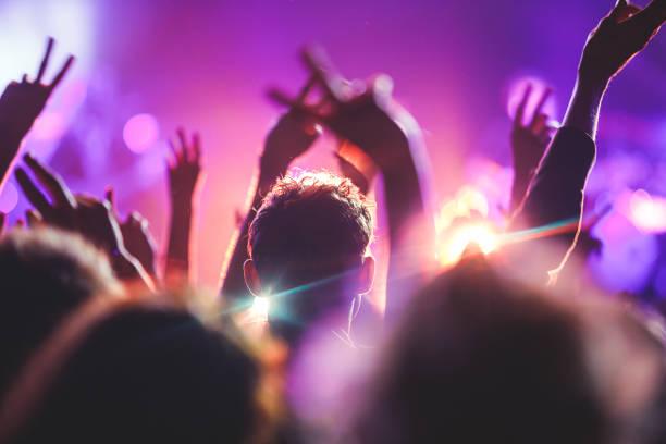 einen überfüllten konzertsaal mit bühne szenenlicht rock-show mit menschen silhouette - popmusiker stock-fotos und bilder