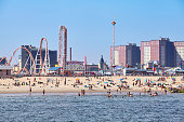 New York, USA - July 02, 2018: Crowded Coney Island beach and amusement parks seen from the pier on a sunny day.