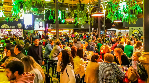 Crowded Food Court, Montevideo, Uruguay MONTEVIDEO, URUGUAY, OCTOBER - 2019 - Crowd at Mercado de la abundancia, a traditional renovated food and drink court of montevideo cirt, uruguay full stock pictures, royalty-free photos & images