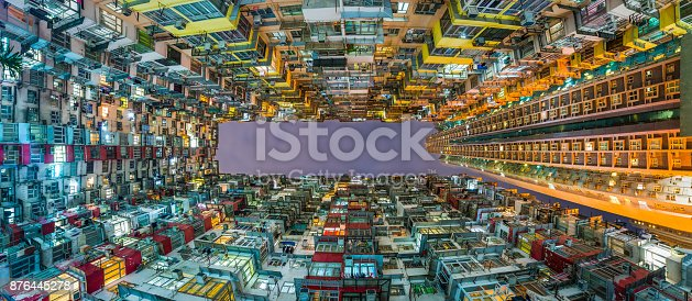Vertical view through the closely packed balconies and warm domestic lights of a crowded apartment block complex to the night sky of Hong Kong SAR, China.