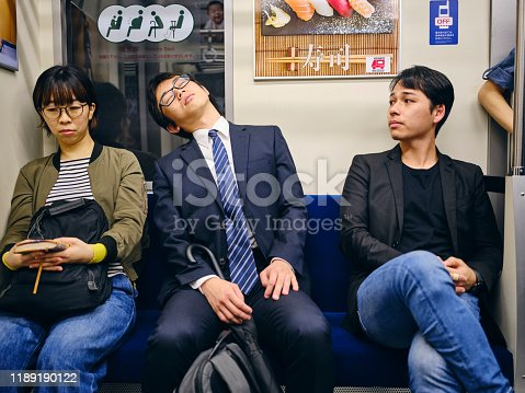 A crowd of people on a Japanese subway train. Fully property released location.
