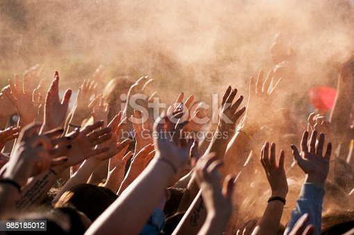 Crowded people hands up at a day time concert.