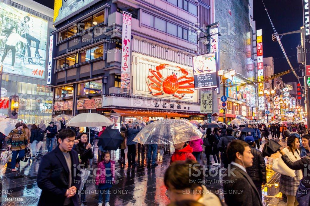 crowded people walking in colorful night raining street in Dotonbori...