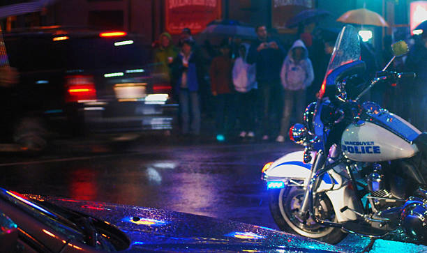 Crowded sidewalk with police motorcycle in foreground stock photo