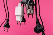 Crowded  white extension cord with many plugs on pink background. The scene is situated in controlled studio environment in front of pink background. Photo is taken with SONY AIII camera