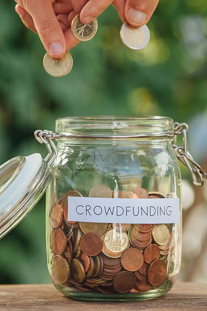 Crowdfunding money jar full of coins stock photo