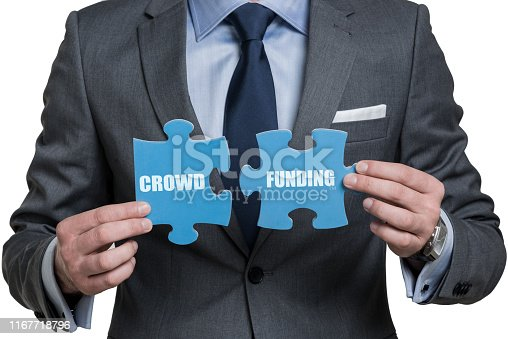 Businessman holding two pieces of puzzle with word Crowdfunding
