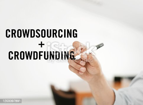 Businessman writing 'crowdsourcing and Crowdfunding' on virtual screen.