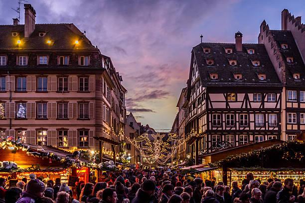 Crowds at Strasbourg Christmas Market Strasbourg, France - December 8, 2013 - Crowds walk up Rue Merciere to the Christmas Market at dusk on December 8, 2013 in Strasbourg. strasbourg stock pictures, royalty-free photos & images