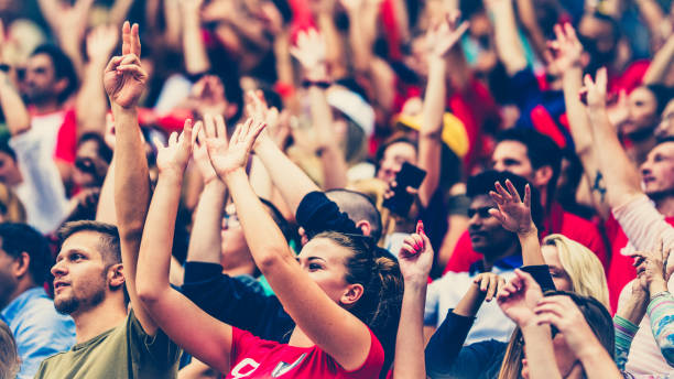 Crowds cheering on a sports stadium Crowd on a stadium cheering with hands up and waving with red balloons. supporter stock pictures, royalty-free photos & images