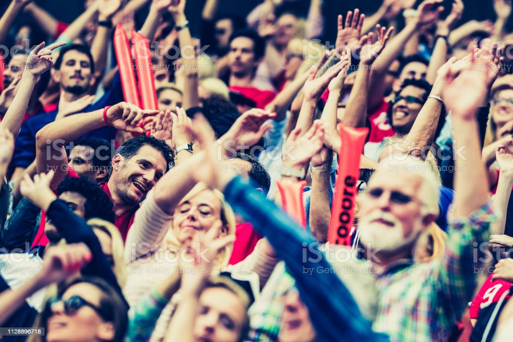 Crowd on a stadium cheering with hands up and waving with red...