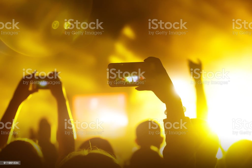 Crowds Enjoying Themselves At Music Festival, smartphone in hands...