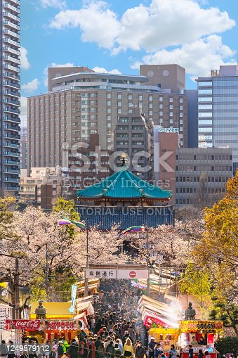 ueno, japan - march 31 2020: Telephoto compression of Bentendo hall of Kaneiji buddhist temple where crowds are gathered between Tekiya stands of Japanese food surrounded by cherry blossoms in Ueno.