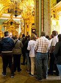 Crowds of people inside the magnificent Saint Peter & Saint Paul Cathedral in St Petersburg, Russia. Some are taking photographs and others are listening to a guided commentary as they look in awe.