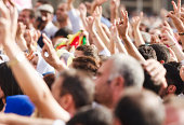 Color image of crowds making peace sign (victory sign) during a protest rally. Selective focus with copy space below.