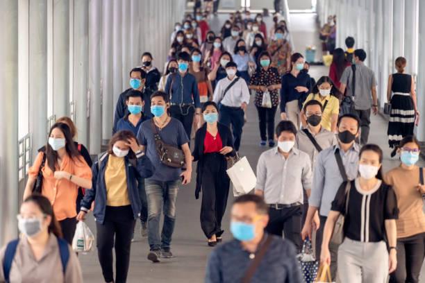 multitudes de personas asiáticas que llevan se enfrentan a la protección contra la infección por el virus coronaso o brote de Covid -19, pandemia y epidemia mientras van a su lugar de trabajo - foto de stock