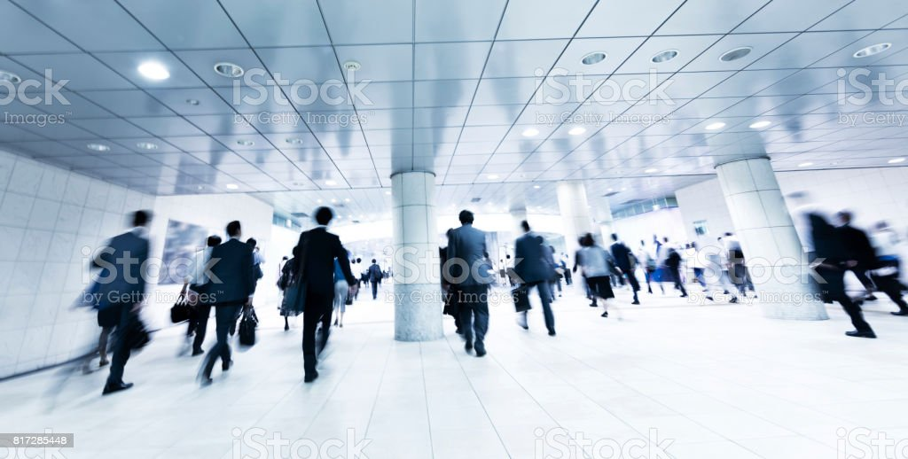 Crowds of Commuters Walking Through Modern Underground Pedestrian Walkway in the Morning stock photo