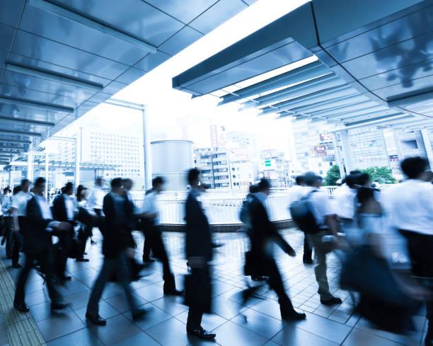 雨の朝に歩行者通路を歩く通勤者の群衆 - 通勤 ストックフォトと画像