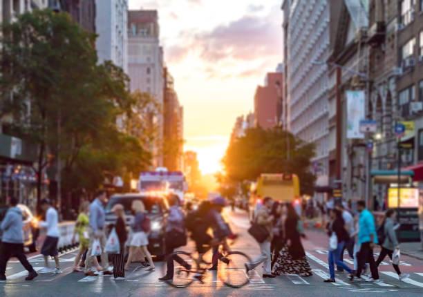 massa's mensen kruis een druk kruispunt op 23rd street en 6th avenue in manhattan met de kleurrijke zonsondergang achtergrond - voetganger stockfoto's en -beelden