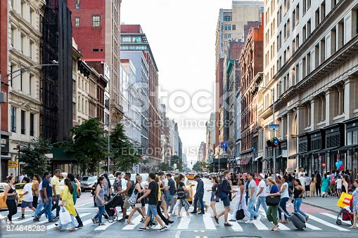 NEW YORK CITY - CIRCA 2017: Crowds of busy people walk across the intersection of 5th Avenue and 23rd Street during the evening rush hour commute in Manhattan, New York City.