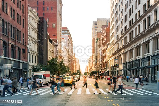 istock Crowds of people walking through a busy crosswalk at the intersection of 23rd Street and Fifth Avenue in Midtown Manhattan, New York City 1279831403