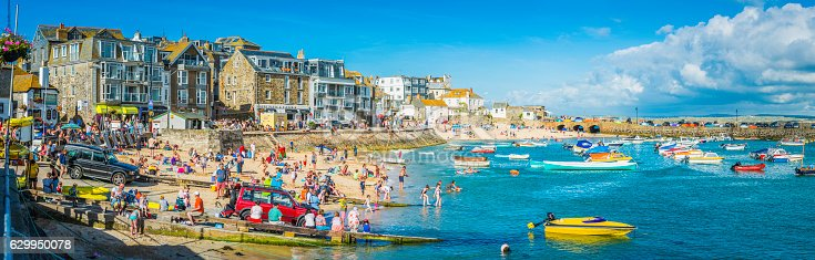 Crowds of holiday makers, day trippers and tourists enjoying the summer sunshine on the popular harbour beach of St. Ives, Cornwall.