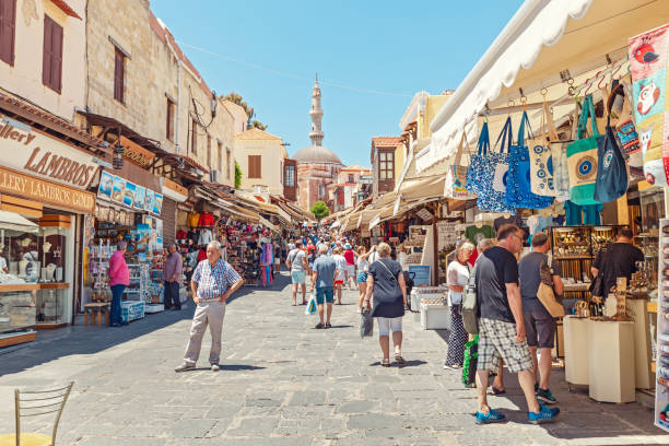 Crowds of tourists walking and shopping at market street in Rhodos town, leading to famous Mosque stock photo