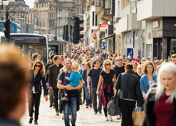 Crowds on busy British shopping street in summer Edinburgh, UK - August 20, 2015: Pedestrians walking on Princes Street in central Edinburgh, one of Scotland's busiest shopping streets. princes street edinburgh stock pictures, royalty-free photos & images