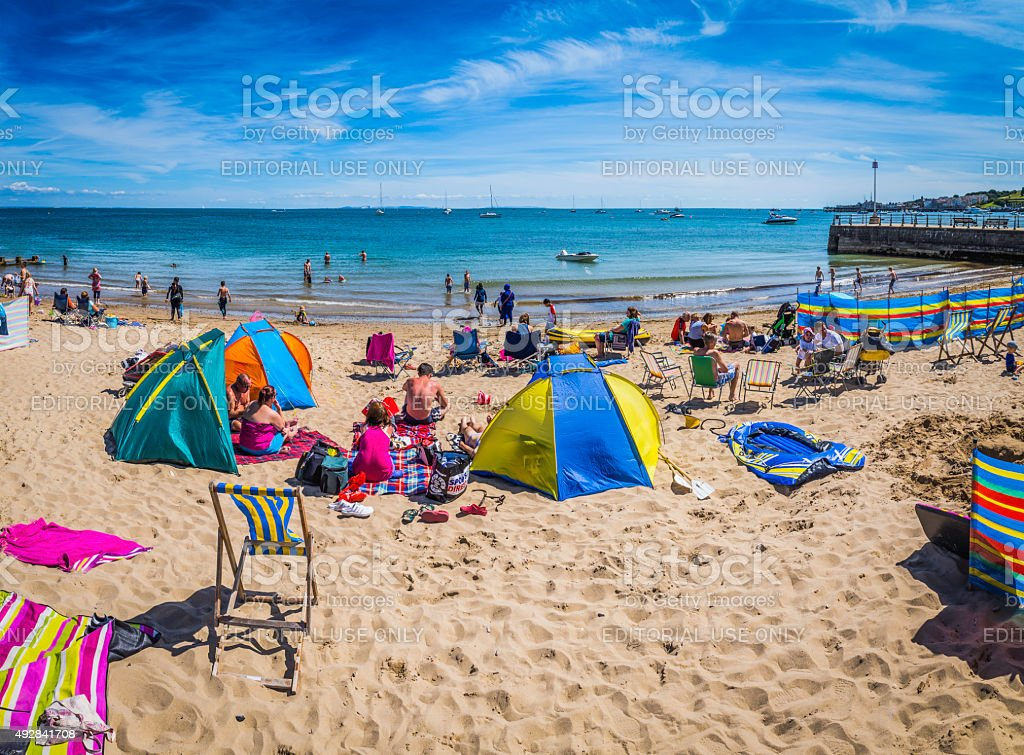 Crowds sunbathing on sandy ocean beach with colourful tents England stock photo