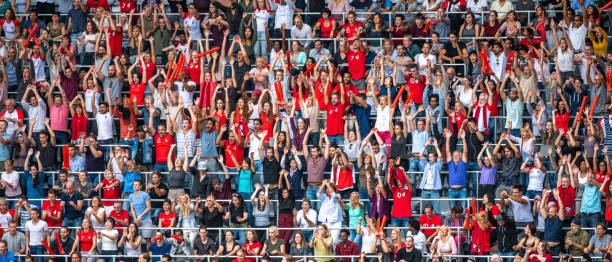 Crowds with hands up cheering their team Large crowd on a football stadium cheering for their team with their hands raised waving and clapping. supporter stock pictures, royalty-free photos & images