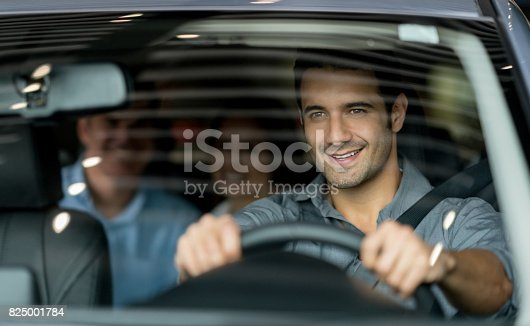 Portrait of a happy crowdsource taxi driver driving a couple of customers - lifestyle concepts
