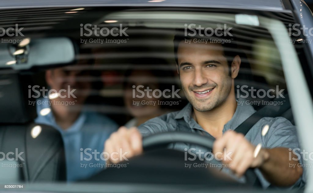 Crowdsource taxi driver driving a couple of customers stock photo