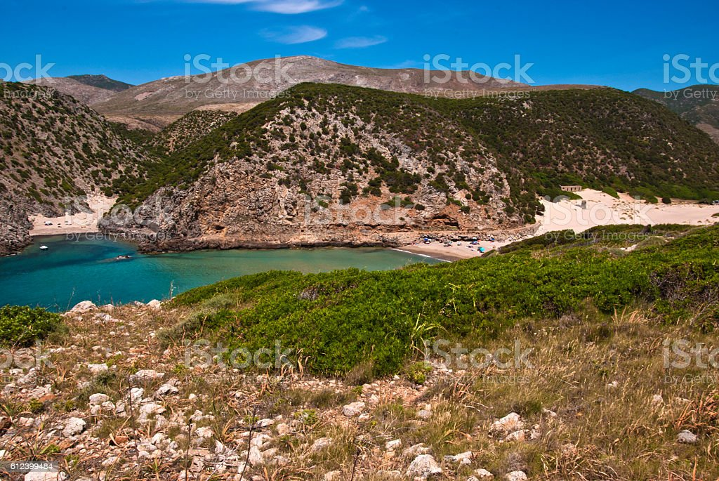 Crowed Cala Domestica beach and promontory. West Coast Sardinia stock photo