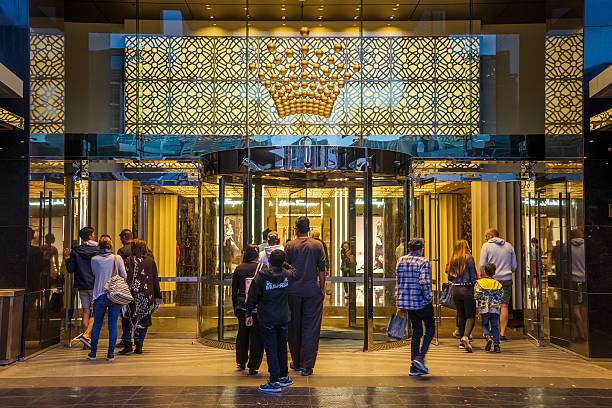 Crown Melbourne Melbourne, Australia - December 20, 2016: Groups of visitors passing through a entrance to the Crown Melbourne integrated resort in Southbank at dusk. entrance sign stock pictures, royalty-free photos & images