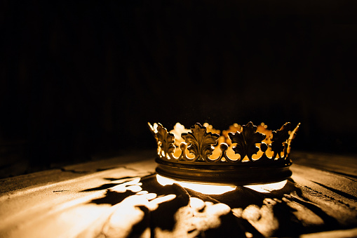 The crown on a black background is highlighted by a golden ray. Game of Thrones.