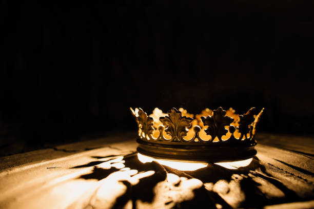 Crown of the real king on a black background. Game of Thrones. The crown on a black background is highlighted by a golden ray. Game of Thrones. crown headwear stock pictures, royalty-free photos & images