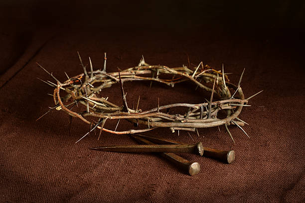 Crown of Thorns and Nails on Cloth Crown of thorns and nails on cloth with dramatic lighting sharp stock pictures, royalty-free photos & images
