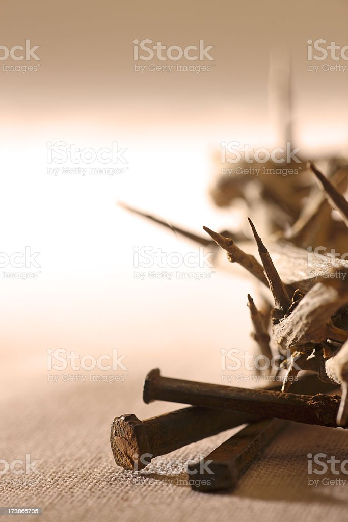 Crown of thorns and three nails on textured golden surface stock photo