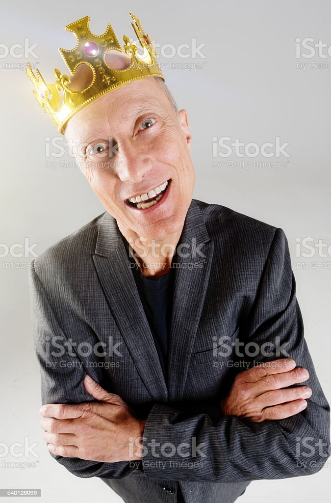 Crowned businessman smiles, satisfied and successful, arms folded stock photo
