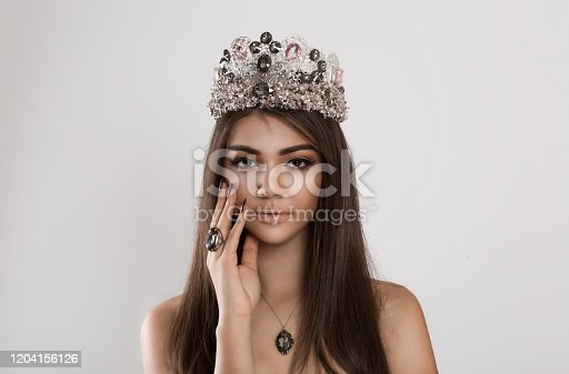 Crowned dark beauty queen. Brunette woman fashion model girl shiny makeup eye shadow lipstick, crystals set earring necklace ring crown looking at camera showing velvet effect burgundy nails manicure