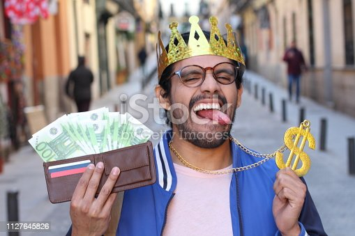 istock Crowned young guy with full wallet 1127645826