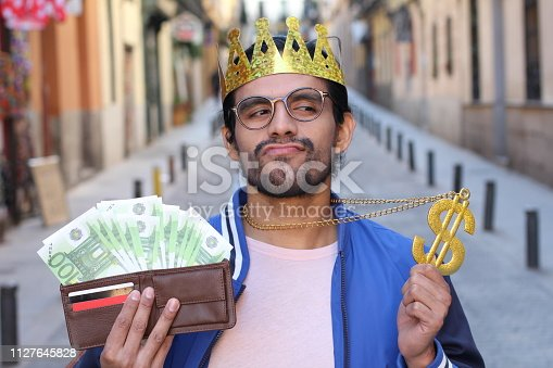 istock Crowned young guy with full wallet 1127645828