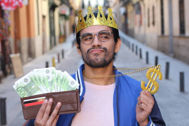 crowned young guy with full wallet - principe persona nobile foto e immagini stock