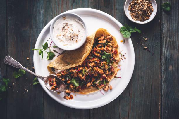 crêpes salées de poi's chiches, poulet gebakken à l ' harissa et kale pour la chandeleur - hartig voedsel stockfoto's en -beelden