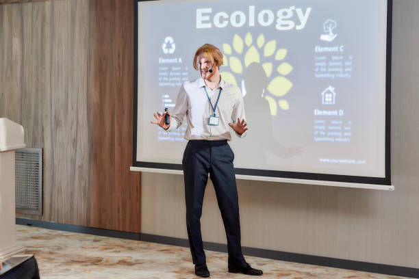 crucial topic. full-length shot of young male speaker in suit with headset and laser pointer showing the presentation on a screen while giving a talk at business meeting, ecological forum - theatre full of people stage foto e immagini stock