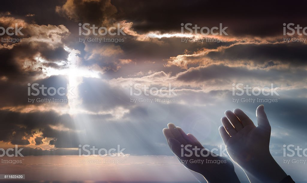 Hands raised to the sky with crucifix of light in the clouds