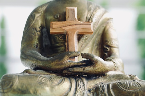 Crucifix In The Arms Of A Buddha Statue Stock Photo - Download Image Now